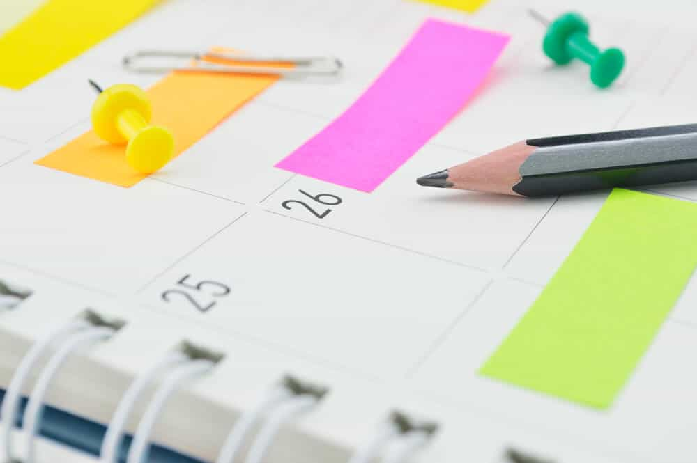 A calendar planner with colorful sticky notes and a black pencil.