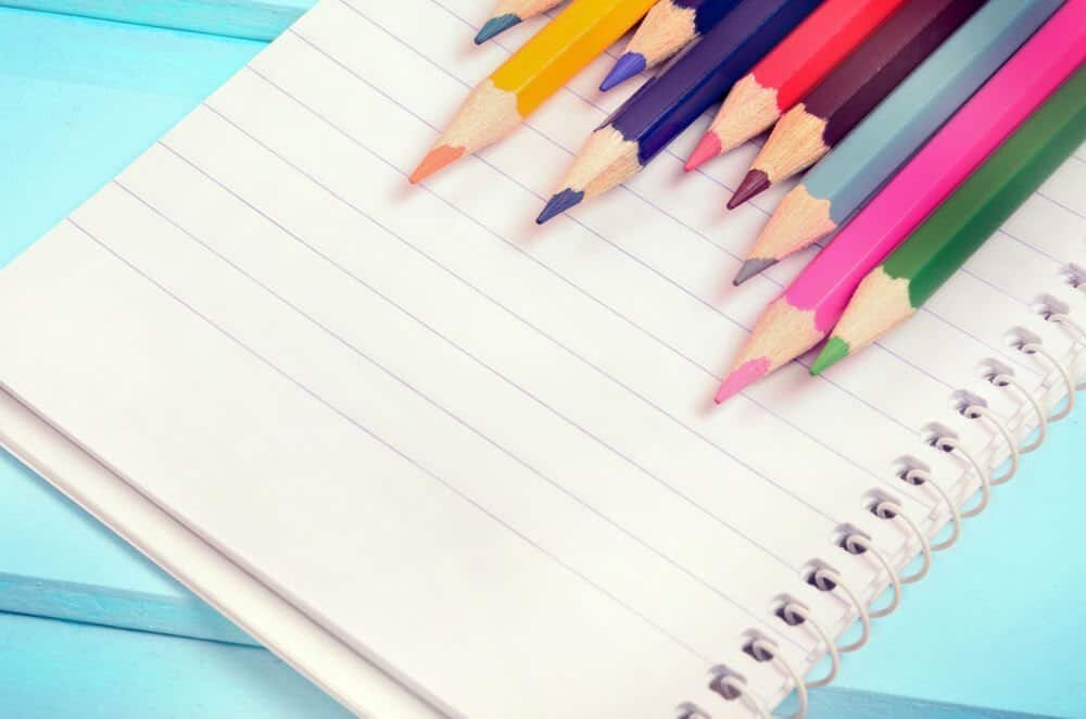 A bullet journal or notebook with colored pencils and a bright blue background.