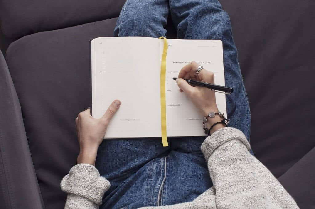A woman journaling in a notebook with a black pen and gold ribbon.